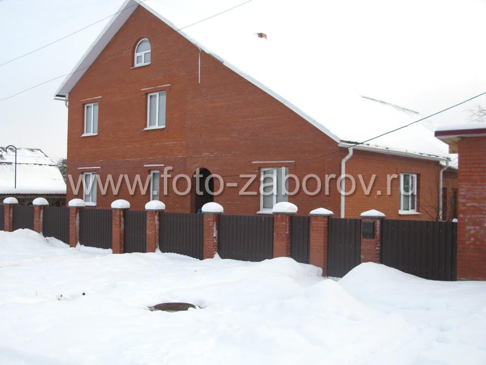 Фото большого кирпичного дома с двускатной крышей, ограждённого забором из