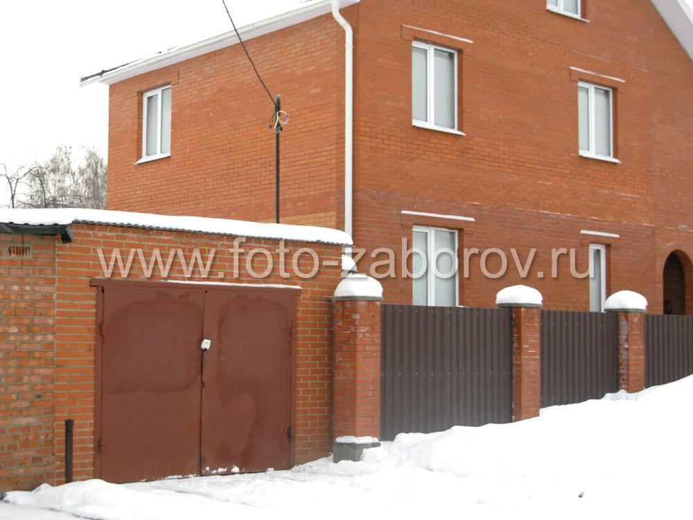 В конце ограды построен одноместный гараж с двустворчатыми воротами из