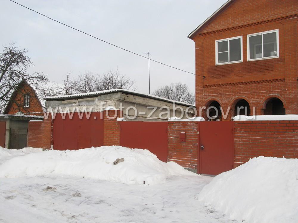 Фото большого частного двухэтажного дома из кирпича под защитой простого кирпичного забора без