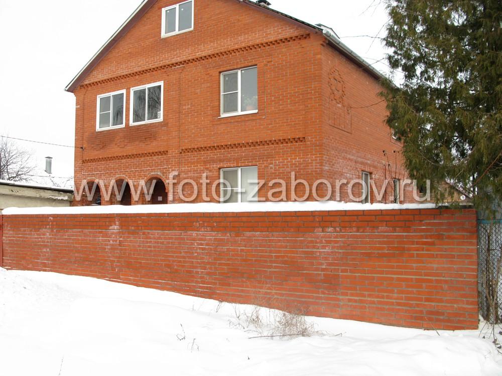 Ограждение сложенное из кирпичей образует сплошную стену вокруг частного
