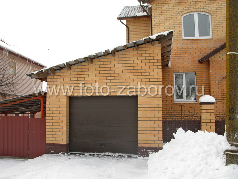 Забор вокруг коттеджа стыкуется с гаражом с односкатной крышей и автоматическими