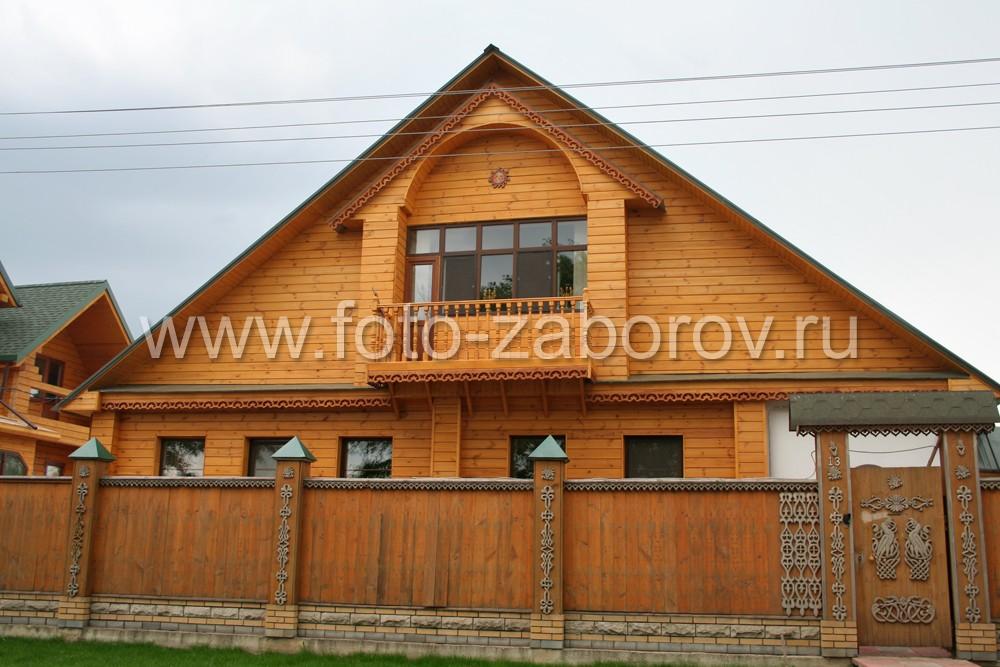 Фото фасада большого деревянного дома из бруса за высоким резным