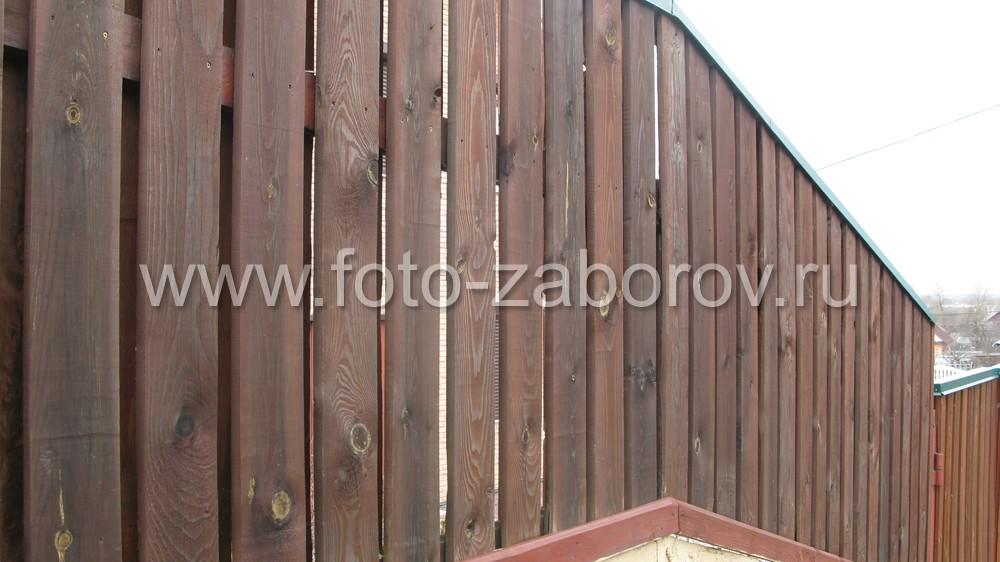 Пример установки деревянного забора на склоне без