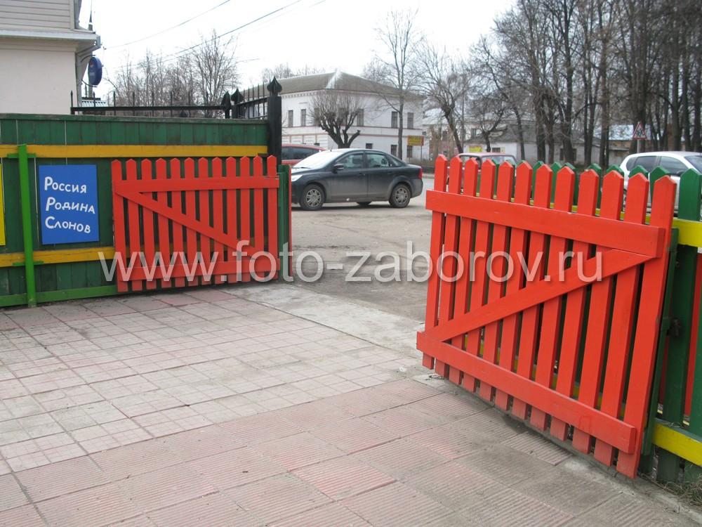 Широкие двустворчатые ворота в деревянном заборе встречают посетителей