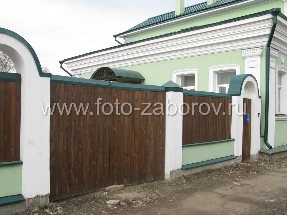 Глухое полотно ворот деревянного забора сделано из вертикальных досок тёмно-коричневого