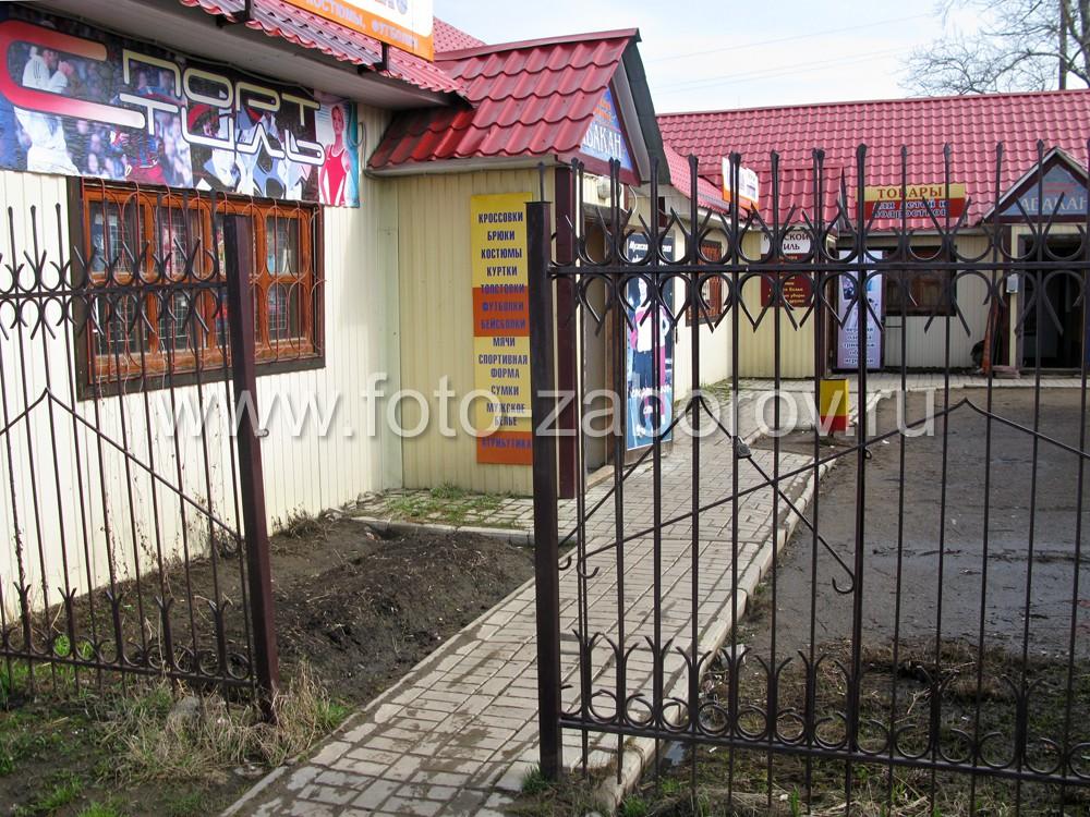 Фото Простенький металлический забор с декоративными эволютами ограждает торговые
