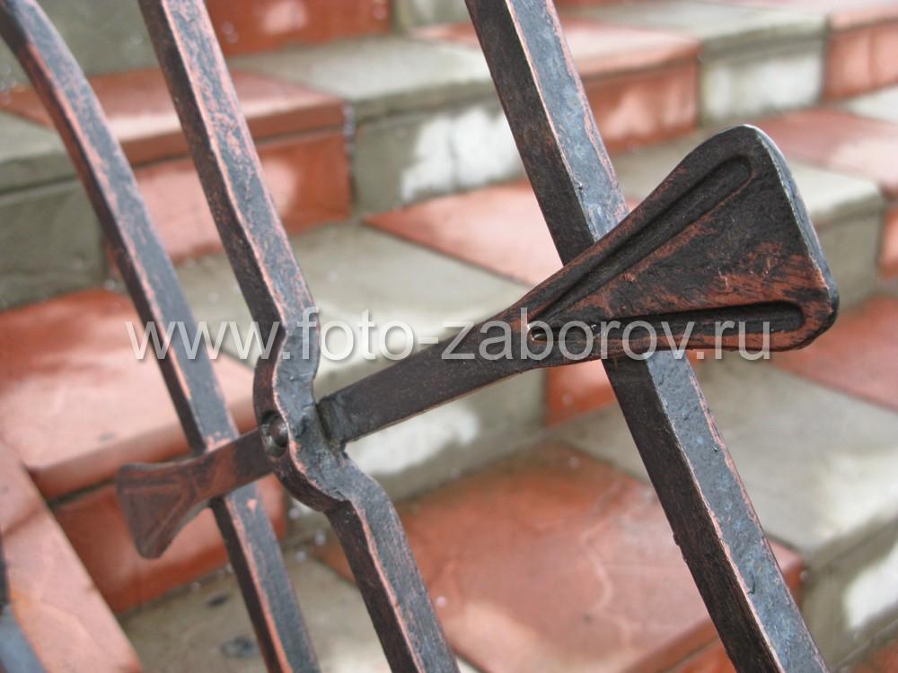 Фрагмент ромбовидной вставки в ограждении лестницы: кованое перекрестье с лапками на