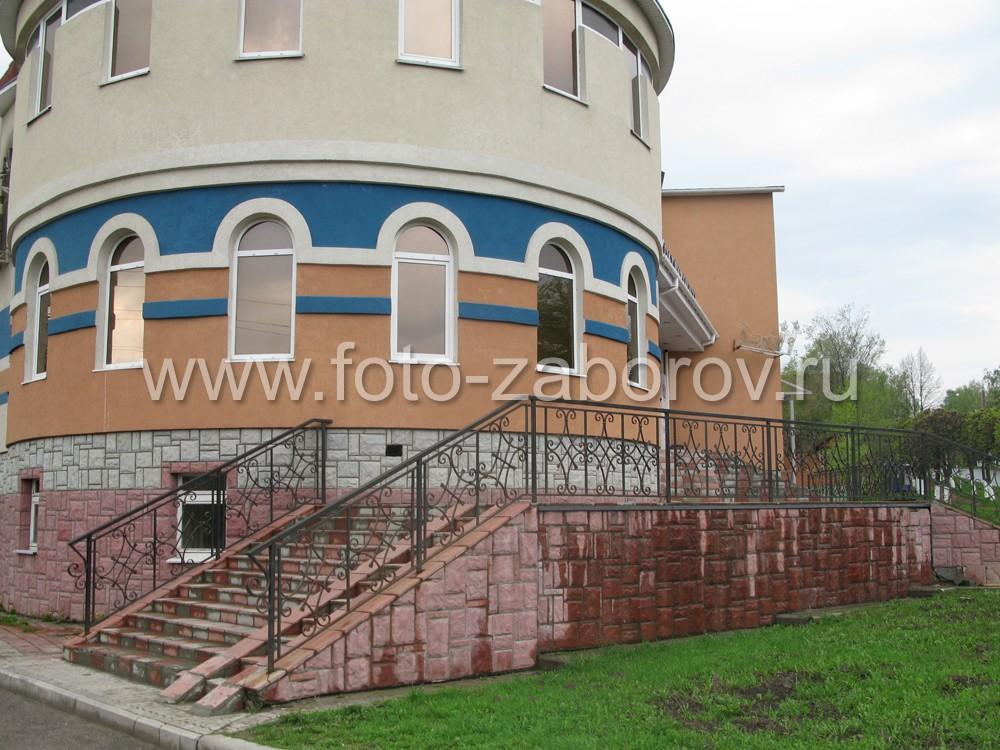 Фото парадной лестницы с мозаичным плиточным покрытием и кованым