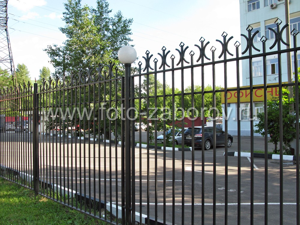 Простая решетчатая ограда площадки у офиса с автомобильной