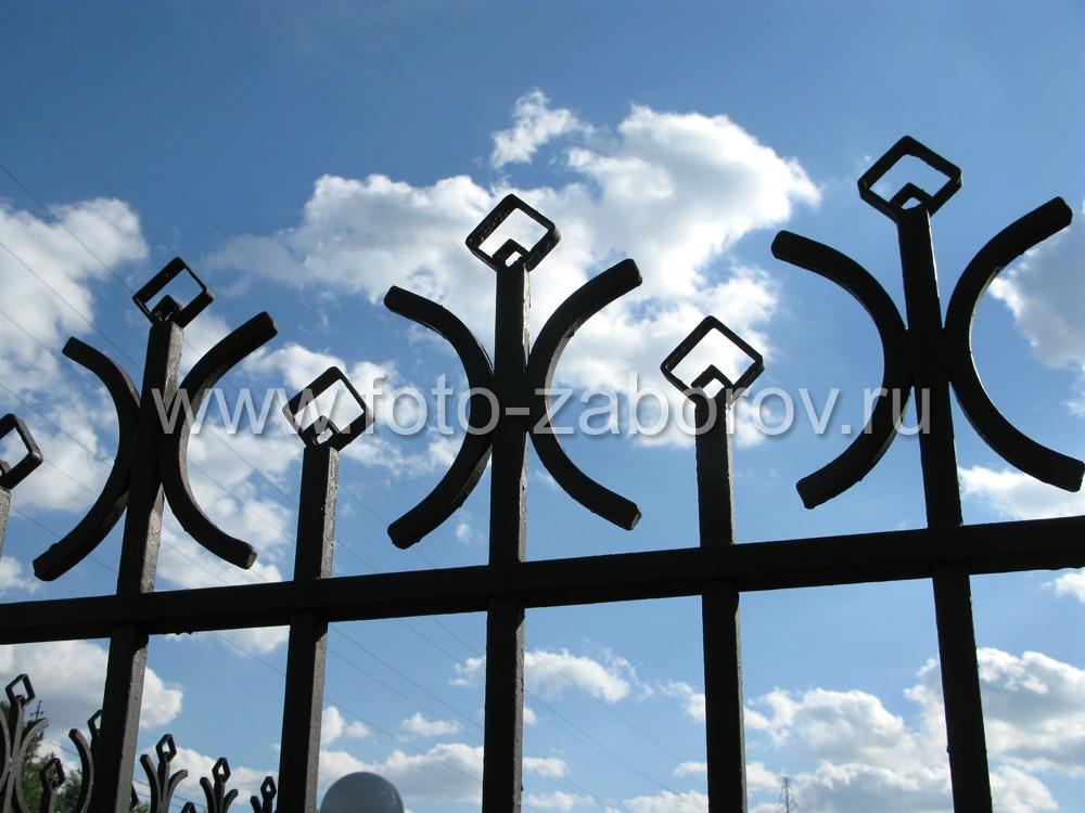 Декоративные элементы металлического забора сделаны из гнутого профиля и резаной трубы квадратного
