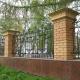 Кованая ограда с массивными кирпичными столбами в окантовке из гранитных плит для городского парка с часовней.