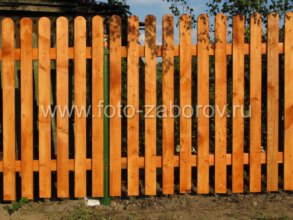 Деревянный забор порывают антисептиком. Можно подобрать цвет антисептика под цвет благородных пород