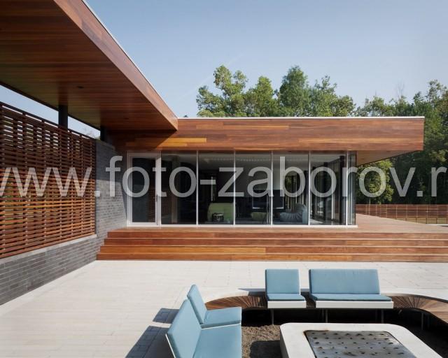 Входная зона имеет стильное деревянное ограждение и кровлю с преобладанием прямоугольных