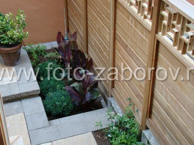 Деревянный забор из шлифованных тонированных досок с деревянным декором-лабиринтом в вехней части