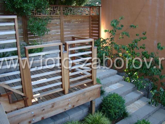 Дизайн внутреннего дворика: деревянный настил на площадках и ограждении лестницы, деревянный забор