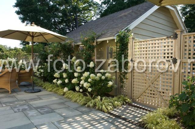 Фото красиво украшенной придомовой территории: цветники разбиты по периметру, ограждённом