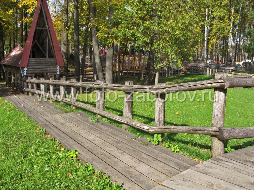 Тропинка с деревянным настилом проходит вдоль забора и у