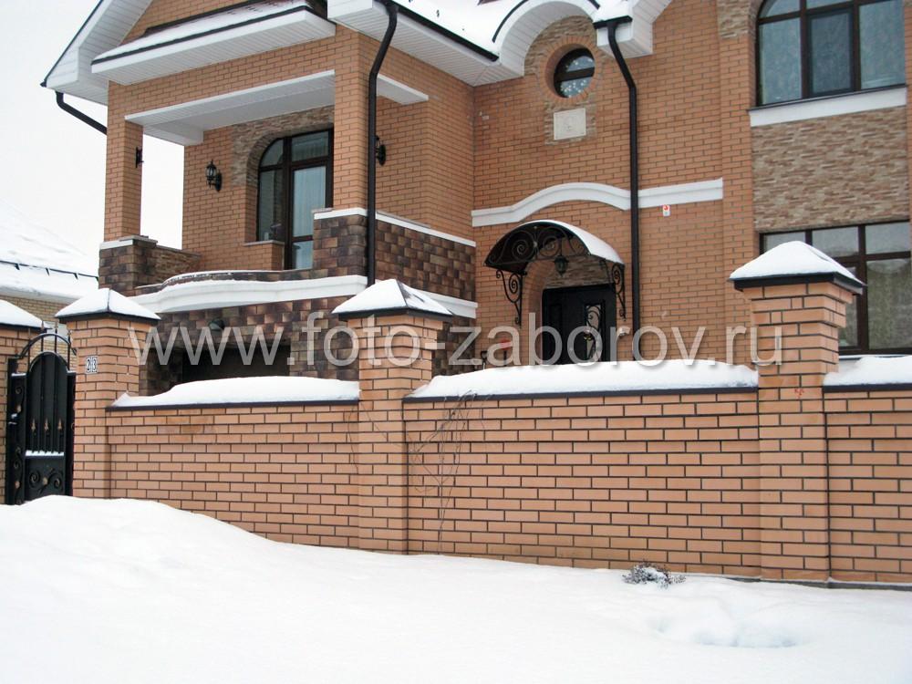 Фасад большого частного кирпичного дома за глухим кирпичным