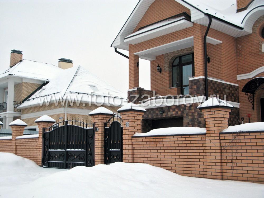 Фасад особняка из жёлтого кирпича ограждён забором в той же