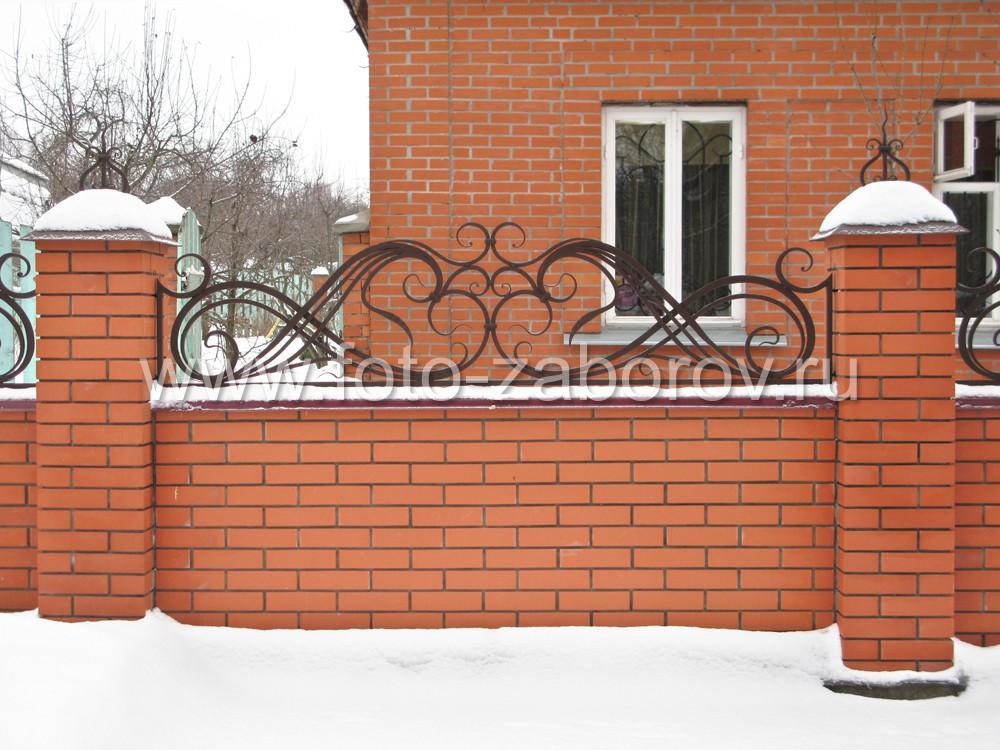 Фото Невысокий забор из красного кирпича с массивными коваными узорами-завитками в верхней части