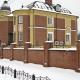 Массивный кирпичный забор для двухэтажного большого частного дома. Жёлто-красная палитра делает морозный зимний день чуть теплее…