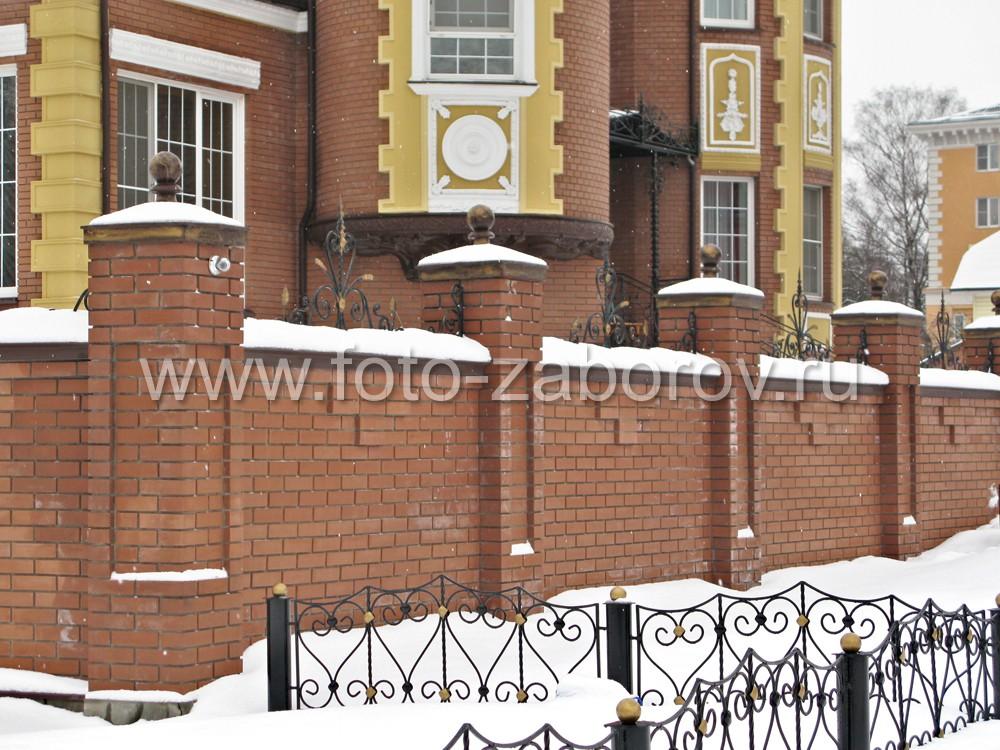 Газоны с внешней стороны забора огорожены аккуратной металлической оградкой с позолоченными шарами