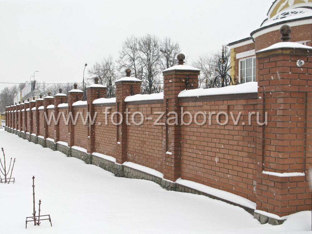 Фотография фасадной стороны кирпичного забора. Кирпичные столбы венчают металлические