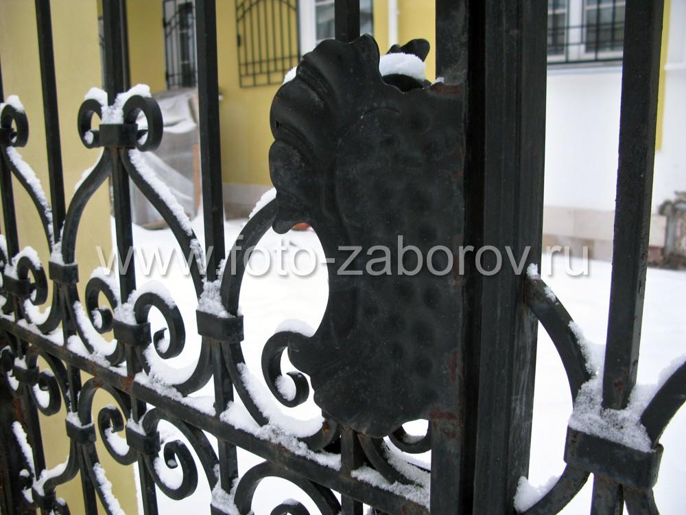 Фото Художественная решётка, украшенная коваными завитками, пиками,