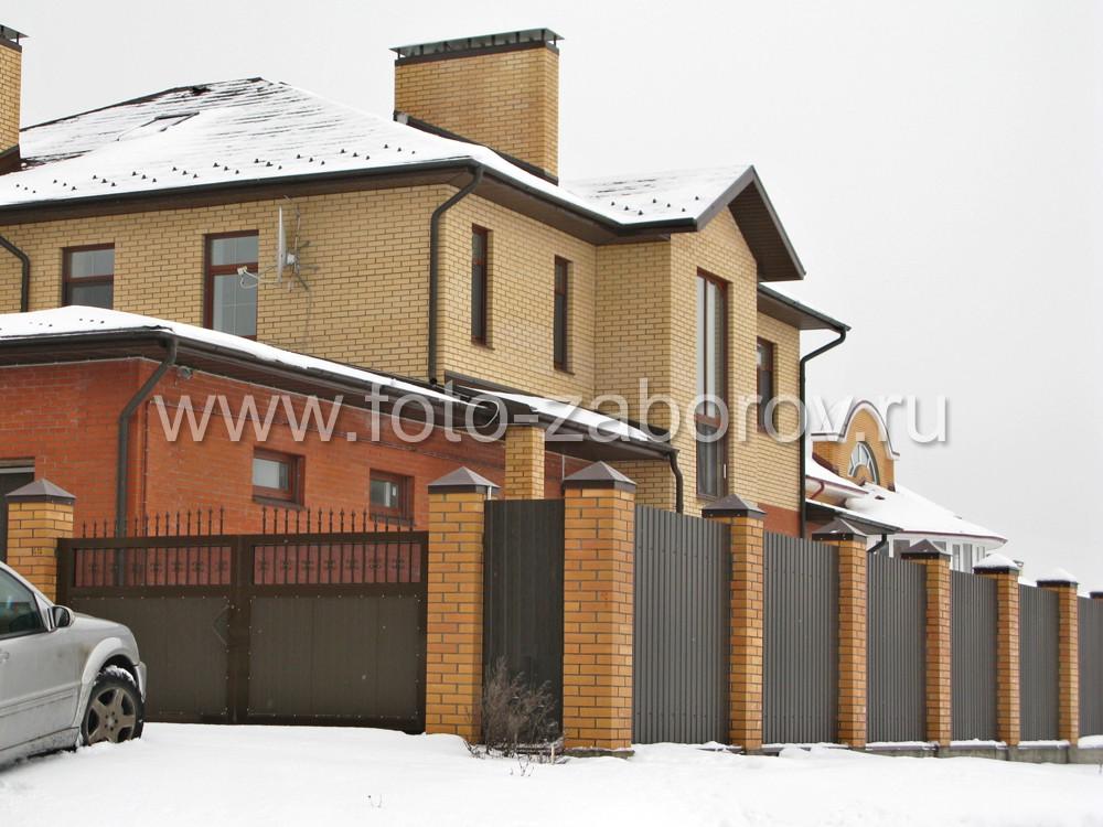 Двухэтажный кирпичный коттедж, огороженный красивым комбинированным