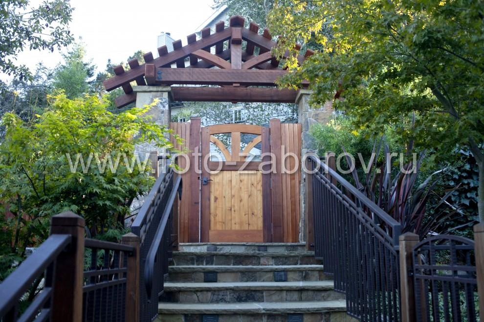 Фото входных ступенек, сделанных из камня. По бокам каменной лестницы установлено деревянное