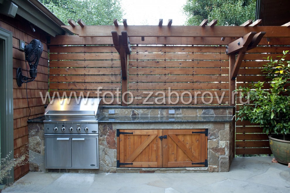 Зону летней кухни ограждает высокая деревянная стена из горизонтального планкена, декорированная по