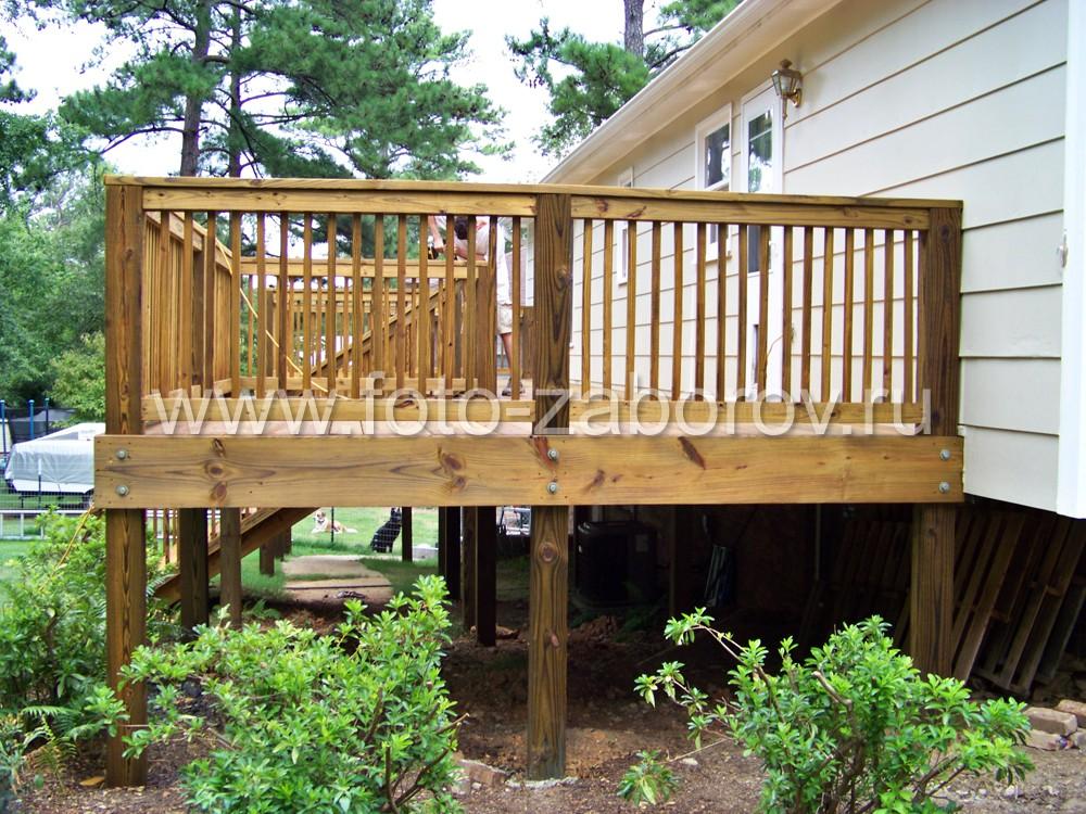 Высокий цоколь коттеджа обязывает использовать в конструкции террасы высокие опорные столбы из
