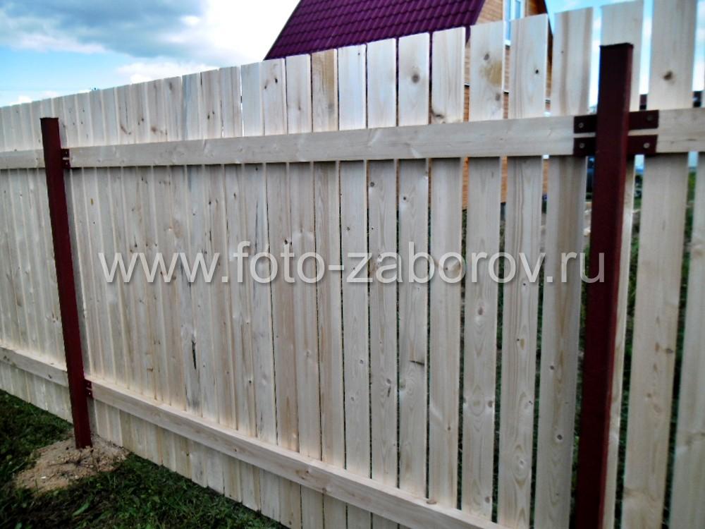 Двухметровый деревянный забор, смонтированный на двух деревянных лагах и металлических столбах с