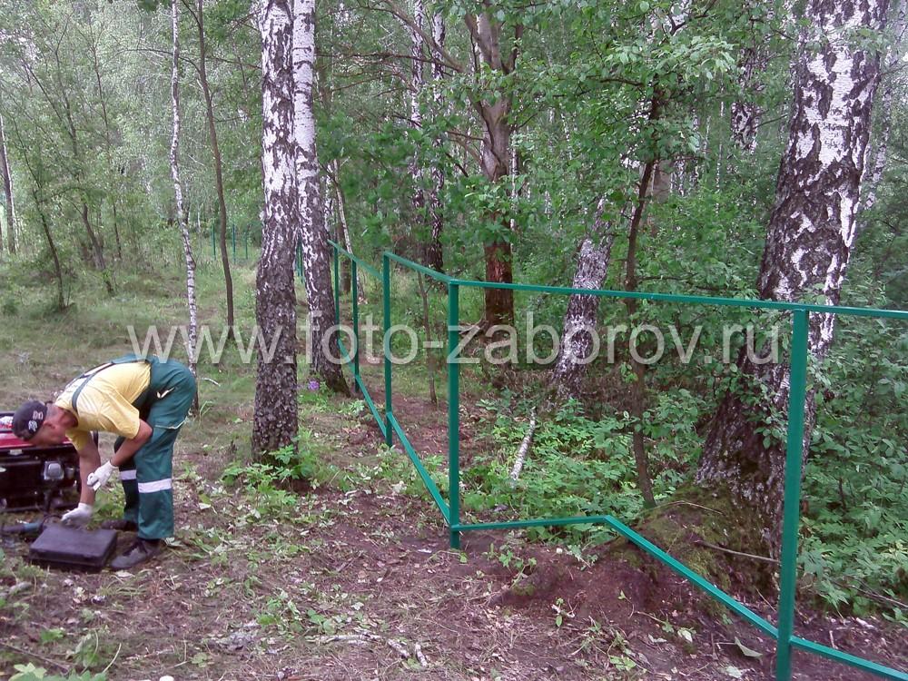Фото Строительство забора из сварной сетки в лесной холмистой местности. Хранитель лесной