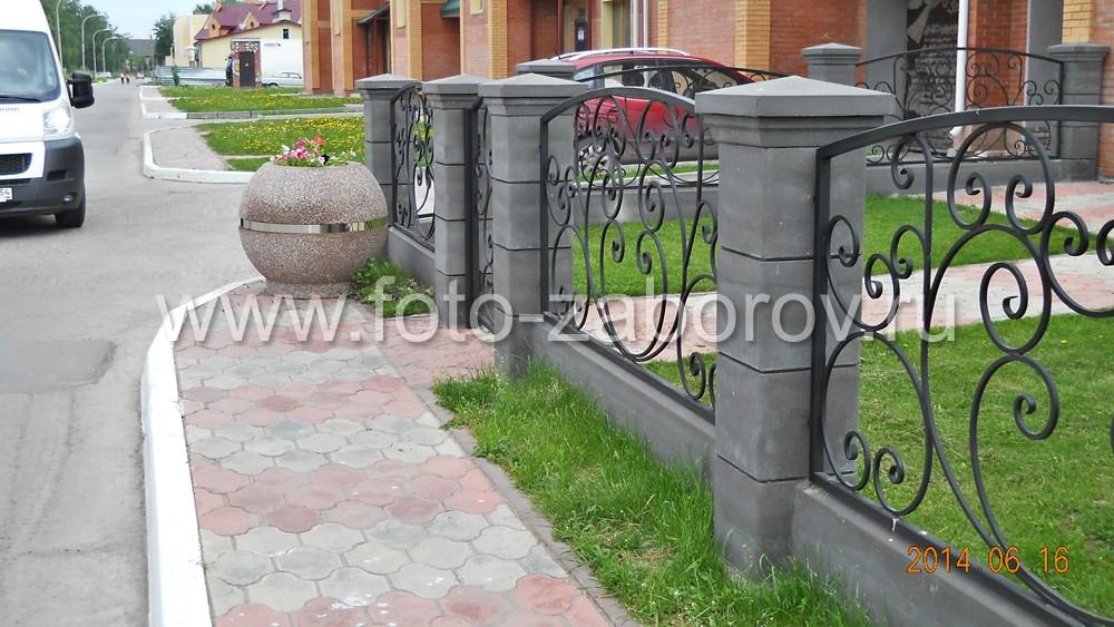 Фото Красивый кованый забор на бетонных столбах в сочетании с габионами и деревянной