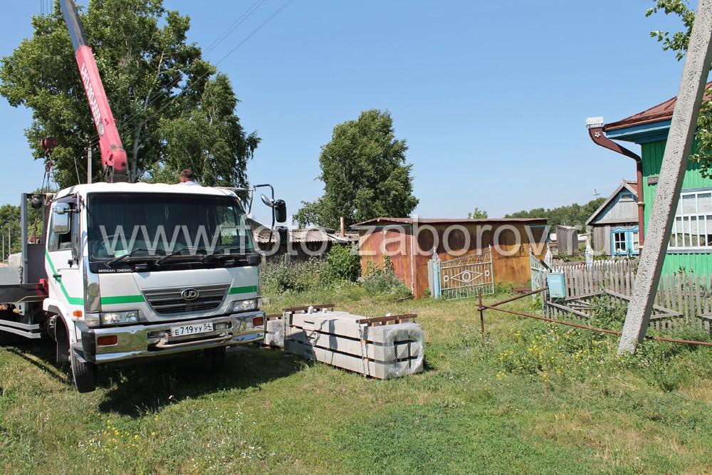 Разгрузка бетонных столбов, доставленных на участок