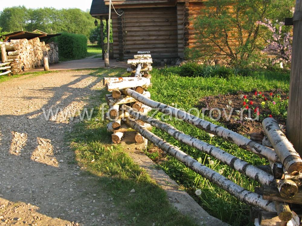 Фото Берёзовая поленница на столбах, берёзовые стволы в пролётах - ограда цветочного палисадника