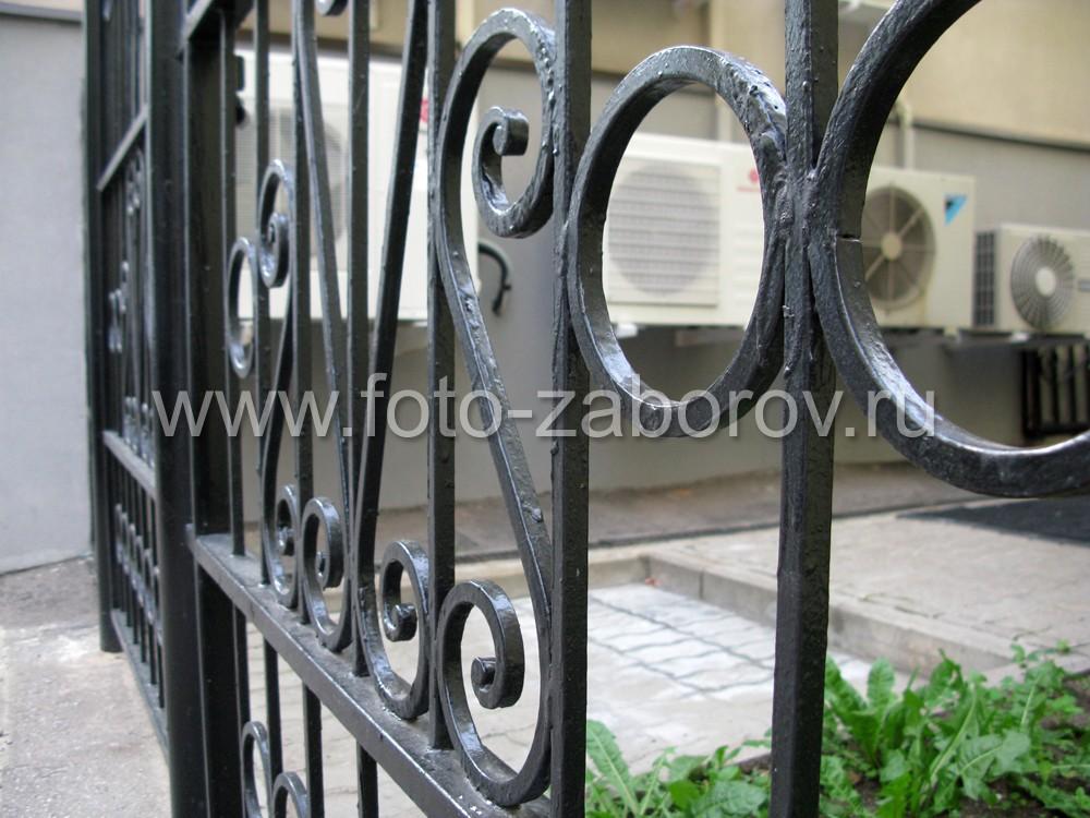 Фото Простой изящный металлический забор с кованым декором. Средняя секция - в виде широкой