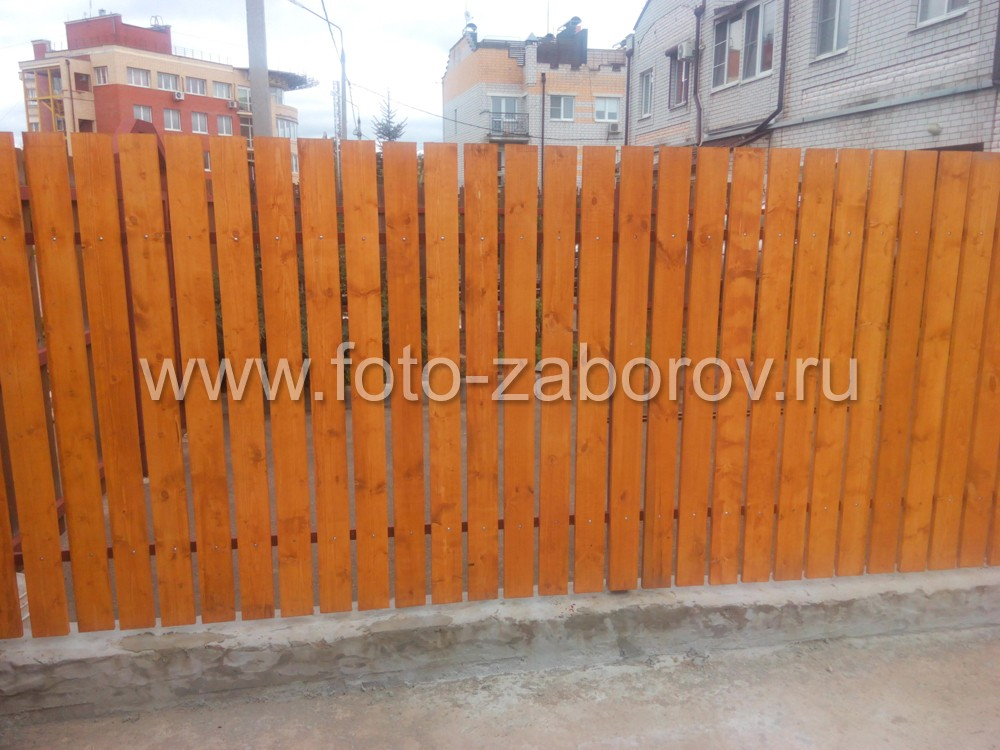 Фото Забор из деревянного штакетника. Монтаж штакетин - с зазором, в основании забора - бетонный