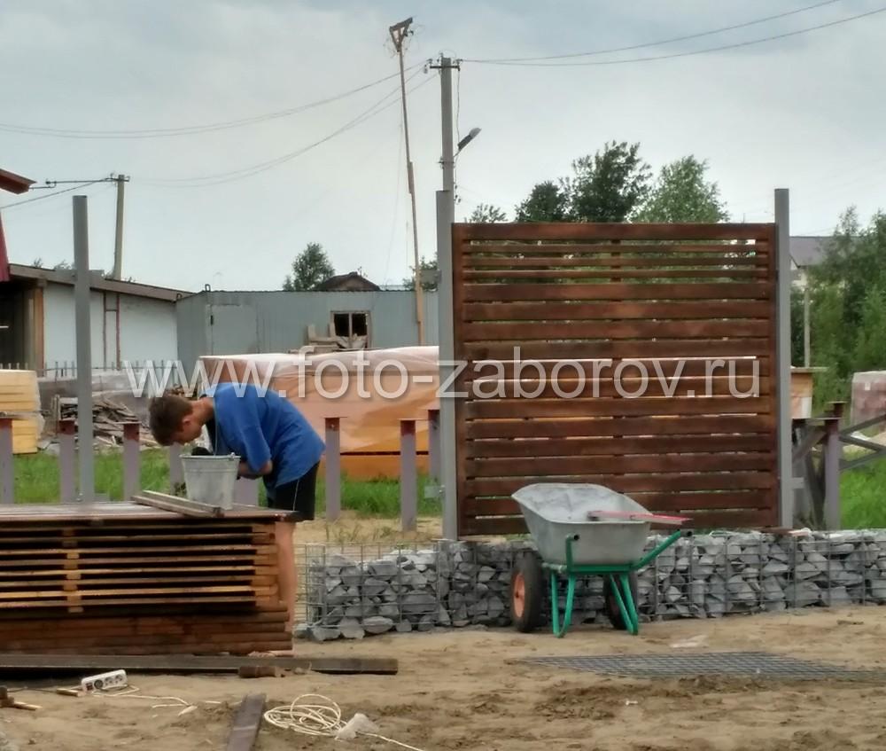 Фото Ограждение - деревянные секции в обрамлении из габионов по краям и в