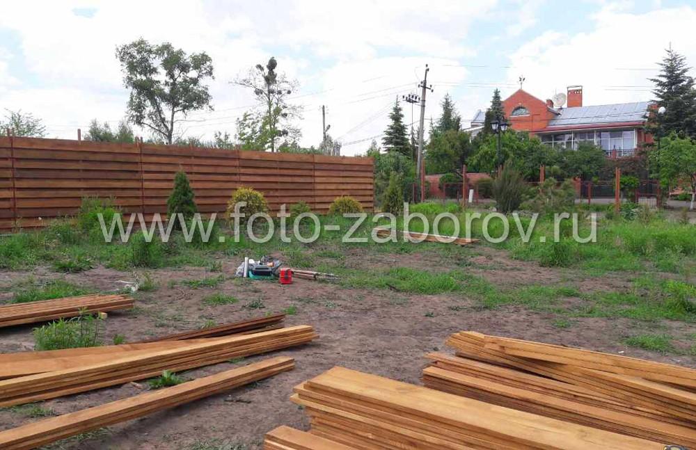 Собраный забор (задний план), строительный нивелир и доски-ламели, готовые к установке на каркас