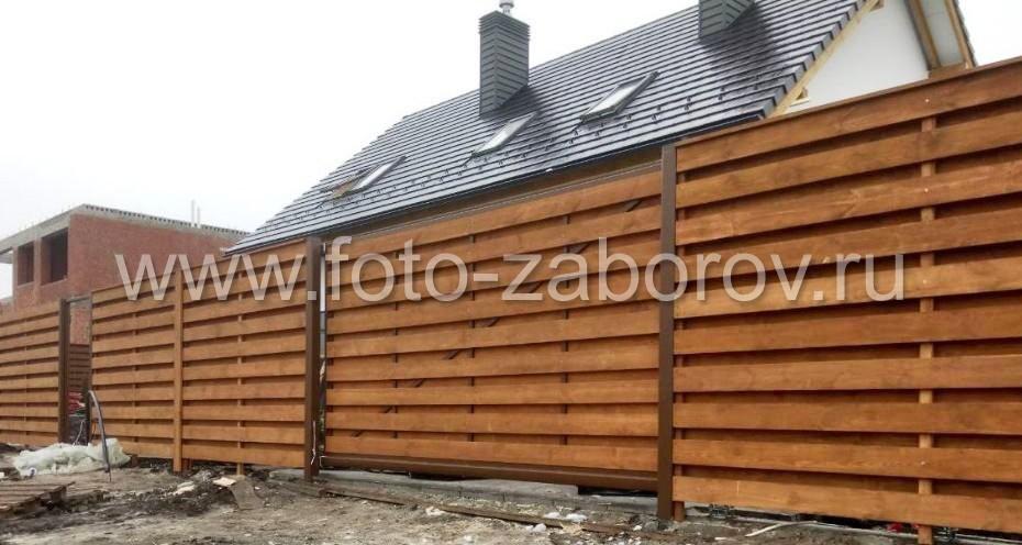 В заборе сооружены откатные ворота, причем в том же стиле - деревянной шахматкой - что и основной