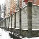 Высокий бетонный забор частного дома, собранный из бетонных плит.